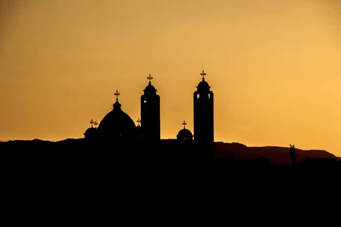 silhouette of the Coptic church on sunset background